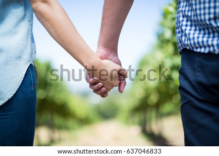 Mid section of couple holding hands in vineyard against blue sky