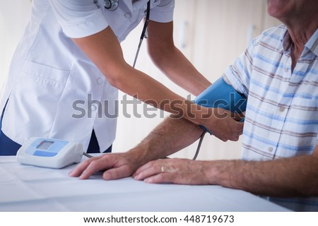 Mid-section of female doctor checking blood pressure of senior man at home