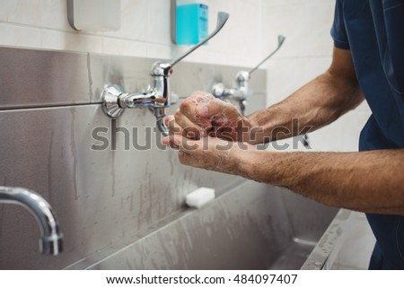 Mid section of male surgeon washing his hands at the hospital