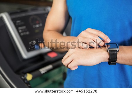 Mid section of man using smart watch on treadmill at gym