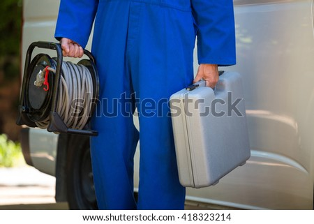Mid section of mechanic with a tool box and cable standing near a car - stock photo