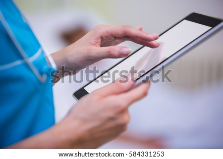 Mid section of nurse using digital tablet in ward at hospital