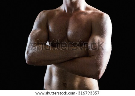 Mid section of shirtless muscular man with arms crossed standing against black background