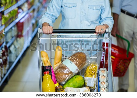 Mid section of smiling senior woman pushing cart at the supermarket - stock photo