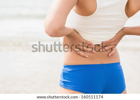 Mid section of sporty woman holding her back standing on beach - stock photo
