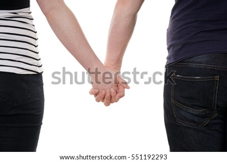 mid section of unrecognizable couple holding hands