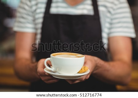 Mid section of waiter offering a cup of coffee in cafe