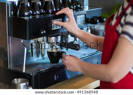 Mid-section of waitress making cup of coffee in cafx92xA9