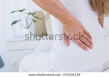 Mid section of woman getting back pain at home in the bedroom - stock photo