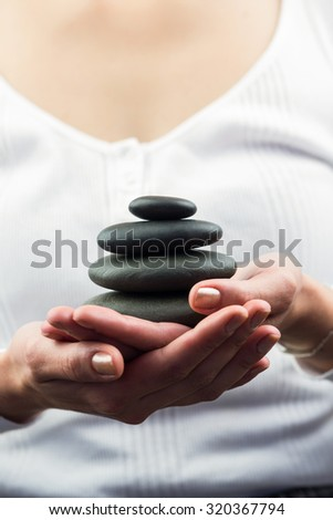 Mid section of woman holding black pebbles in her hand - stock photo