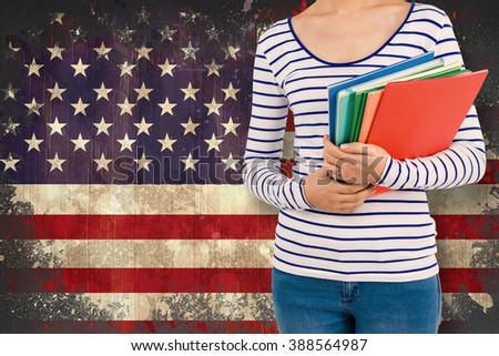 Mid section of woman holding files against usa flag in grunge effect
