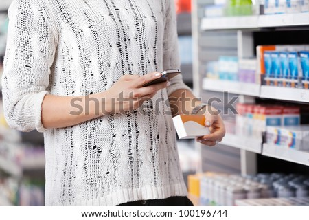 Mid-section of woman holding medication box and dialing on cell phone - stock photo