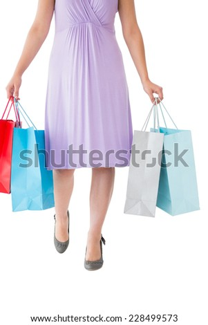 Mid section of woman holding shopping bags on white background