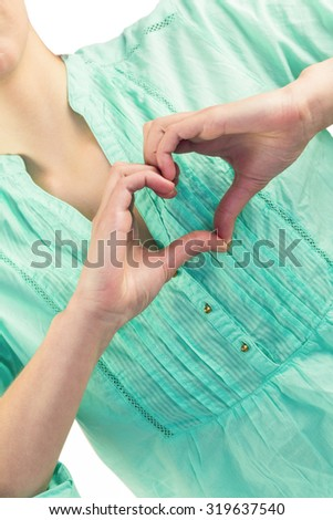 Mid section of woman with heart shape of fingers against white background - stock photo