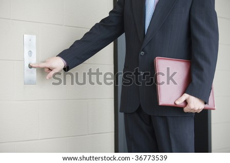 Mid section view of a businessman pressing button for elevator in an office building - stock photo