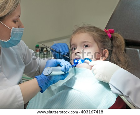 Mid section view of a dentist examining a girl teeth - stock photo