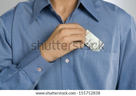 Mid section view of a man putting money in shirt pocket - stock photo