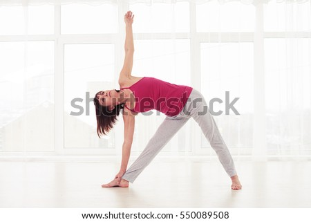 Mid shot of Caucasian female doing workout. Performing an element from yoga or pilates trainings. Standing on the yoga mat in the gym