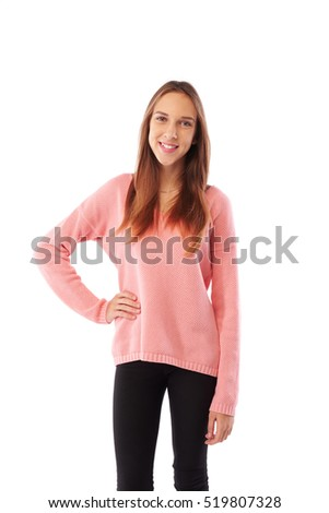 Mid shot of slender young girl with hand on hip posing over white background. Young sensual beauty teenager girl in casual pink sweater posing in studio