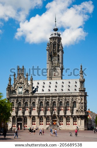 MIDDELBURG, THE NETHERLANDS - JULY 1, 2014; Unidentified people in front of the famous city hall of Middelburg on July 1 in Middelburg, Zeeland, The Netherlands,   - stock photo