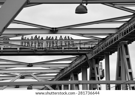 MIDDELFART, DENMARK - MAY 23, 2015: Bridge with bridge-walking bridge and a group of people in gray coveralls on guided tour on top of the Old Little Belt Bridge. - stock photo