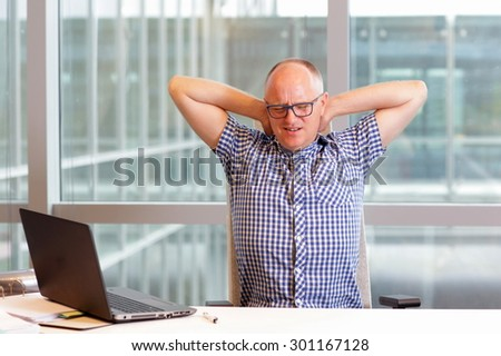 middle age balding man with pain in the neck stretching arms in his office - stock photo