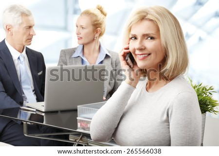 Middle age business woman making call while her colleagues working at background with laptop. Business team banking on line.  - stock photo