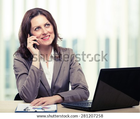 Middle-age business woman talking on the mobile phone in office. Portrait of smiling business woman. Toned photo - stock photo