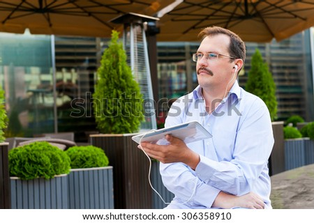 Middle age businessman listen music from tablet pc outdoors