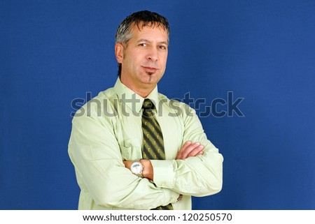 Middle age caucasian business man, can be boss, manager or other employee, arms crossed with little smile on his lips, studio shot over blue background. - stock photo