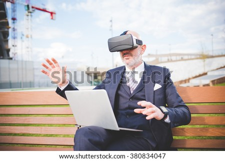 Middle age caucasian business man sitting on a bench with laptop on his knee using smart watch and 3D viewer - futuristic, multitasking, technology concept