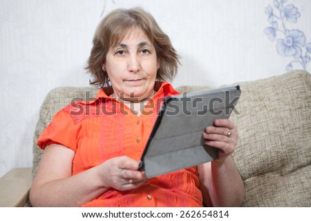 Middle age Caucasian woman holding tab and looking at camera