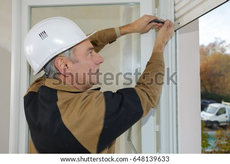 middle-age construction worker installing window in house