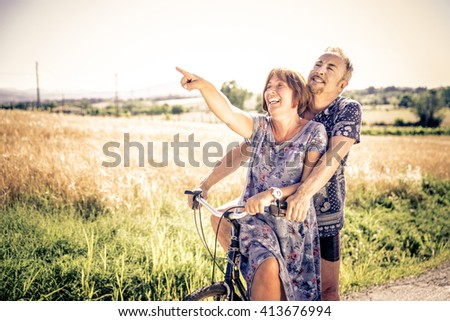 Middle age couple going for a ride with the bicycle in the countryside - Senior couple having fun outdoors - stock photo