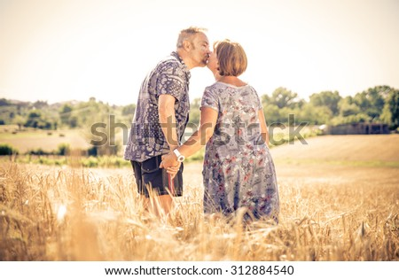 middle age couple kissing each other in a wheat field. concept about middle age couple and relationship - stock photo