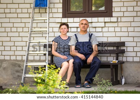 Middle age couple sitting on the bench near country house - stock photo
