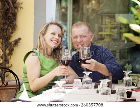 Middle age couple with glasses of red vine enjoying a sunny day in Lucca, Italy  - stock photo