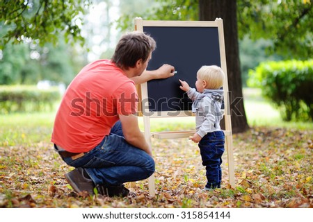 Middle age father and his toddler son at blackboard practicing mathematics