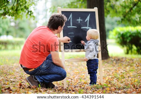 Middle age father and his toddler son at blackboard practicing mathematics  - stock photo