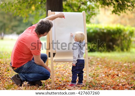 Middle age father and his toddler son drawing on white empty paper