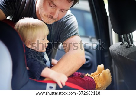 Middle age father helps his toddler son to fasten belt on car seat