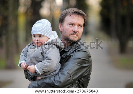 Middle age father with his toddler son walking outdoors / kidnapping concept - stock photo