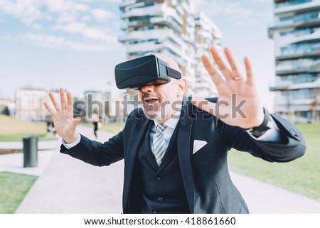 Middle age half length caucasian business man using smart watch and 3D viewer - futuristic, multitasking, technology concept - stock photo