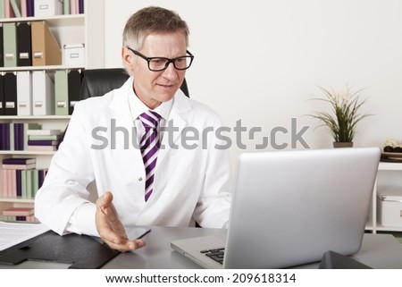 Middle Age Health Professional Talking Clients Progress using Laptop
