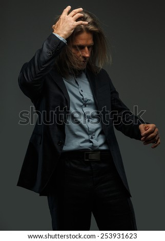 Middle age male in a suit possing in studio. Isolated on grey background.