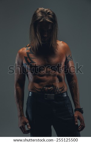 Middle age male with long hair and naked torso possing in studio. Deep shadows. - stock photo
