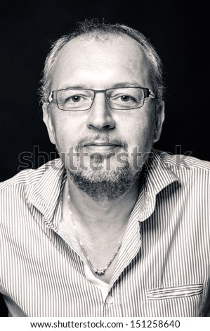Middle age man close up portrait against black background. Black and white image.  - stock photo