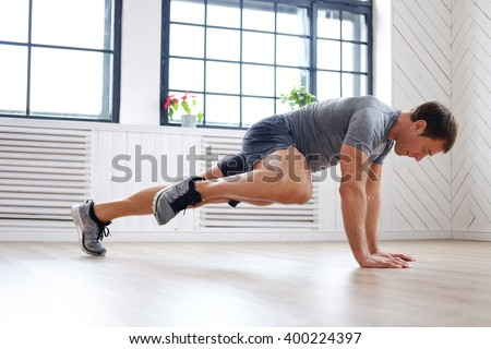Middle age man in a grey t shirt doing abs workouts on the floor.
