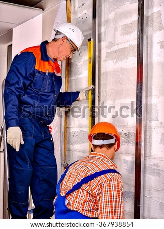 Middle age man in builder uniform with his learner indoor. - stock photo