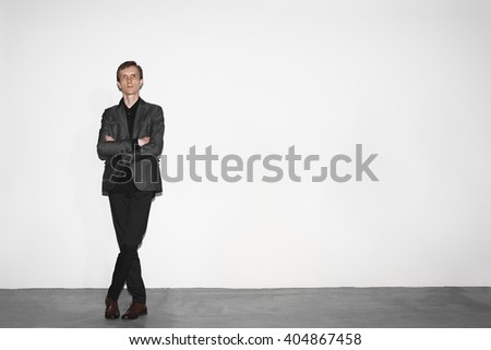 middle age man in gray wool jacket and brown shoes standing near white concrete wall with crossed hands - stock photo